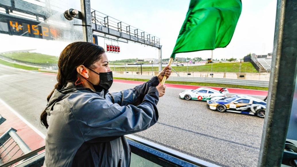 Julie Obreiter of the Cayman Islands Department of Tourism Waves the Green Flag on Porsche Carrera Cup North America Presented by the Cayman Isands - COTA - Race 1, 2021, PCNA