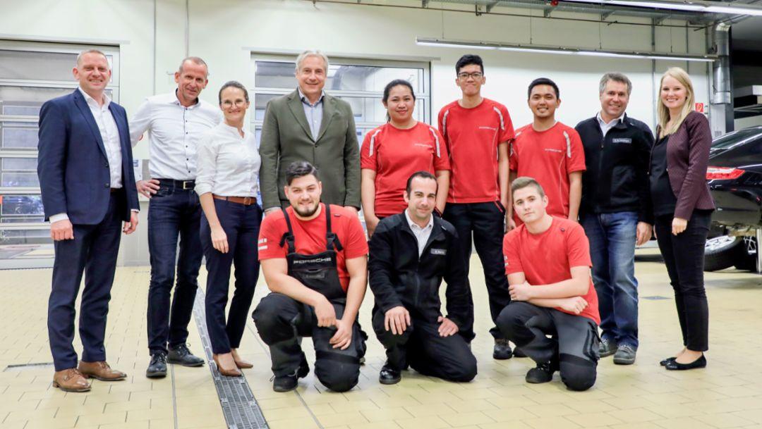 Three young Filippinos in the workshop of the Porsche Centre Stuttgart
