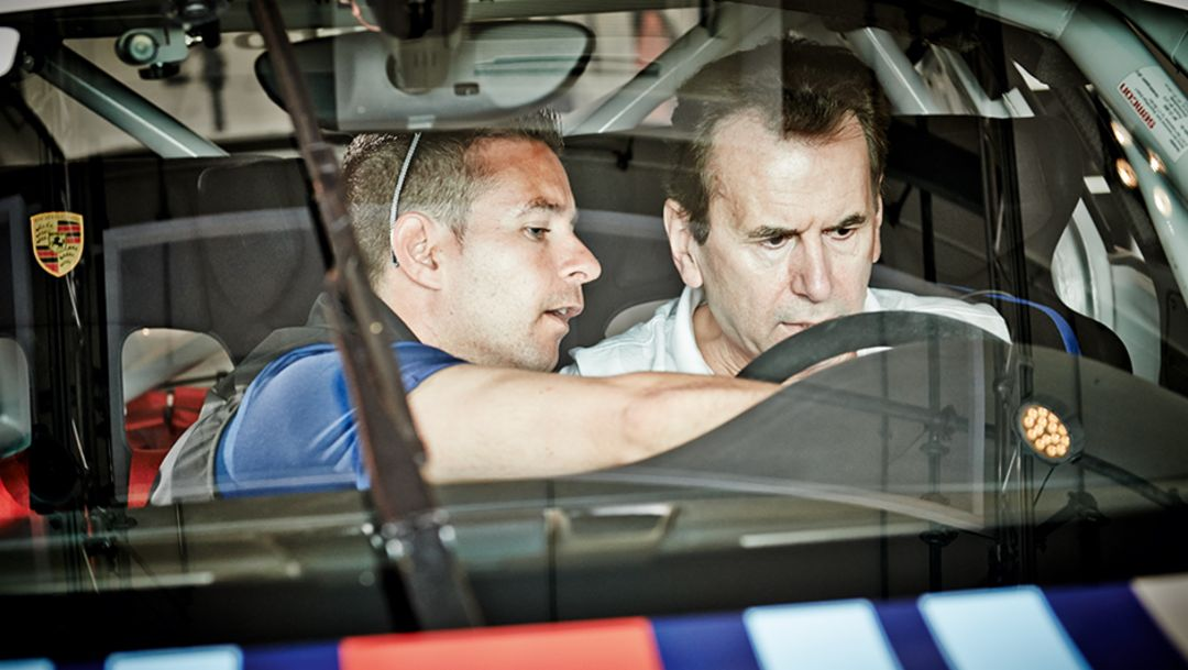 Instructor Manuel Lauck explaining the 911 GT3 Cup dashboard to Karlheinz Blessing
